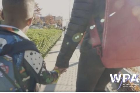 A little boy wearing a back pack holds his mother's hand while walking. The photo is courtesy of Women's Prison Association.