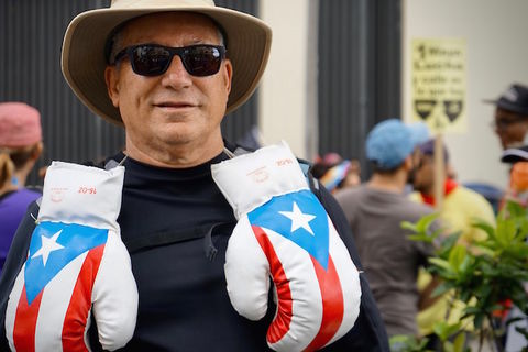 A man wearing sunglasses poses with boxing gloves decorated with the Puerto Rican flag