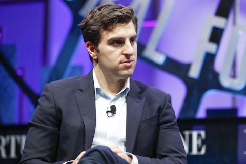 Brian Chesky in navy blazer and light blue dress shirt, purple background