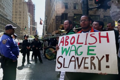 "Man holds sign reading ""ABOLISH WAGE SLAVERY"" while standing alongside other protesters in Manhattan"