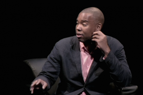 Black man wearing a dark blazer and pink button-down shirt