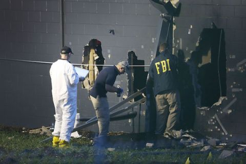 "Three FBI investigators by damage site at Pulse, two in navy jackets with yellow ""FBI"" lettering"