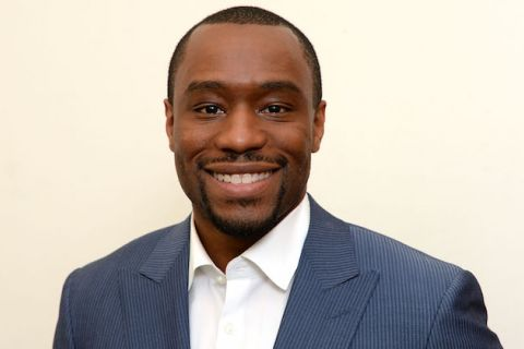 Marc Lamont Hill in navy blazer and white shirt with beige background