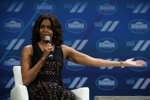 Michelle Obama in black dress with multi-colored pattern, blue background in back