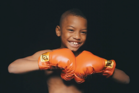 Smiling, shirtless Black boy brings orange boxing gloves together in front of his chest