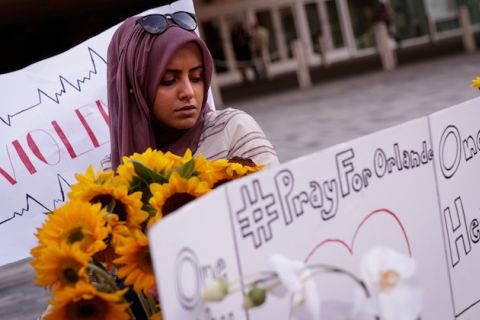 Pulse massacre mourner Saamiya Pirbhai, wearing a rose-colored hijab, stands behind a makeshift memorial with homemade posters and sunflowers.