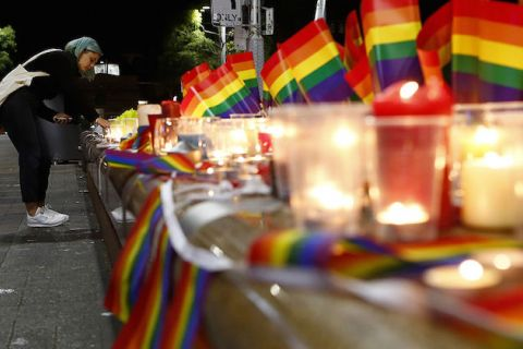 A woman wearing a blue head scarf lights a candle on a long makeshift memorial alter that is dotted with rainbow flags