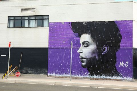 "A purple mural depicts Prince with his eyes closed, it is signed ""Mr. G."""