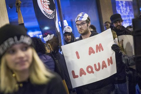 "White man dressed in black stands in crowd of protesters holding white and red sign that says, ""I am Laquan."""