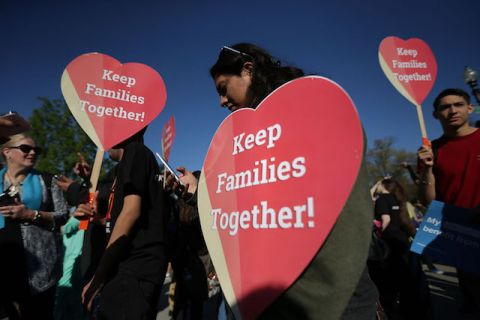 "Women in front of the U.S. Supreme Court hold up red, heart-shaped signs that say, ""Keep Families Together!"""