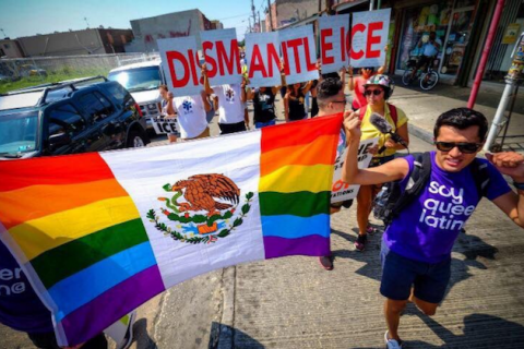 "rainbow/Mexican flag and sign reading ""Dismantle ICE"" in red text with white background"