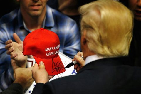 "Man stands with back to camera holding a red hat that says ""Make American Great Again""; man in blue plaid shirt holds out hands to receive the hat"