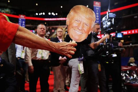 Man holds papr mask with face of Donald Trump