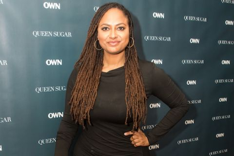 Ava DuVernay in black dress with teal background