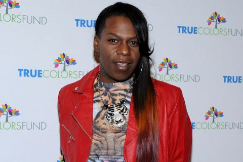Big Freedia in red jacket and orange-and-black tshirt against white background