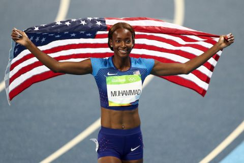 Dalilah Muhammad in navy and green racing outfit, holding red, white and blue American flag