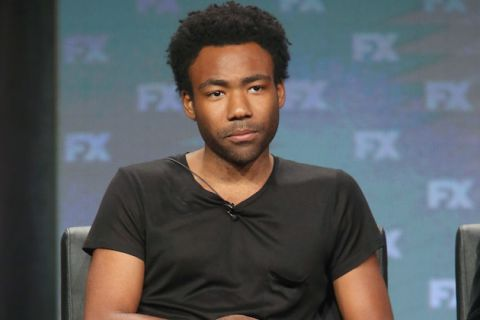 Donald Glover in black t-shirt against blue-gray background