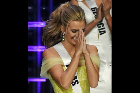 Karlie May in yellow dress with white sash, hands held in prayer formation