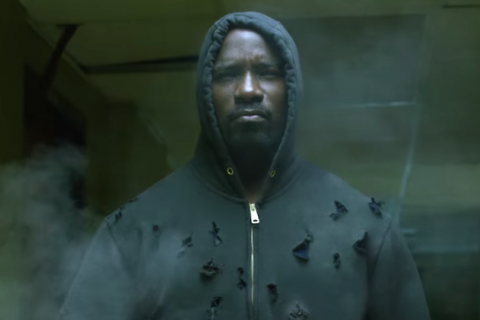 Luke Cage wears a black hooded sweatshirt with bullet holes in it