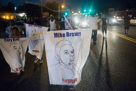 Children march in the street at night, holding white banners with the faces of Michael Brown, Cary Bell and Eric Garner