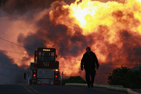 A law enforcement official runs towards a massive fire in San Bruno, California, September 9, 2010, where a pipeline exploded and killed eight people.