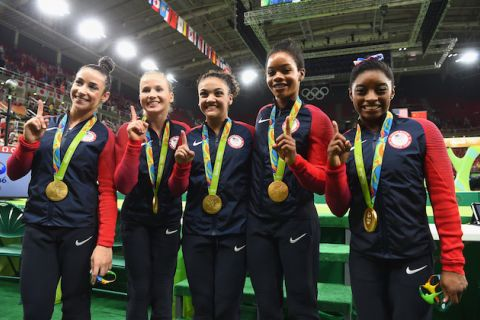 Five Team USA gymnasts in blue, red and white team warm-ups wearing gold medals