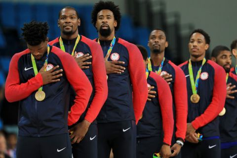 Players in navy and red warm ups with gold medals on green lanyards