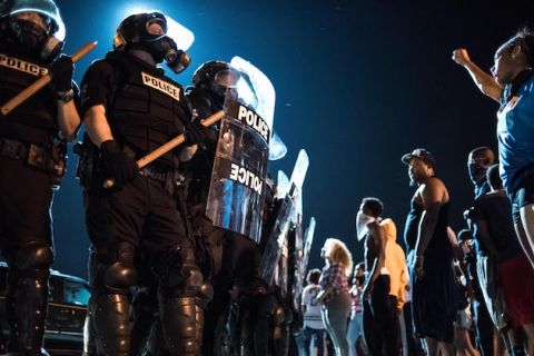 Police in black riot gear near protesters against dark night sky