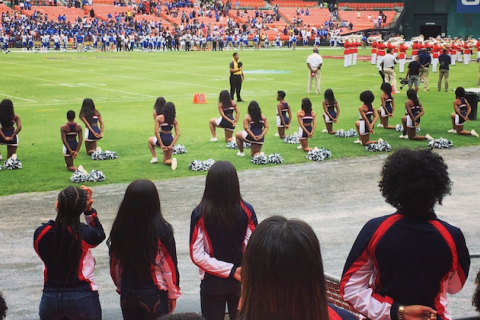 Black women in black cheerleading attire kneeling on green and white football field sideline