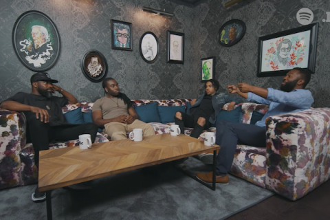 Four black men in black, blue and brown clothing seated on pink and green couch against gray walls