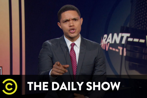 Trevor Noah in grey suit with white shirt and red striped tie
