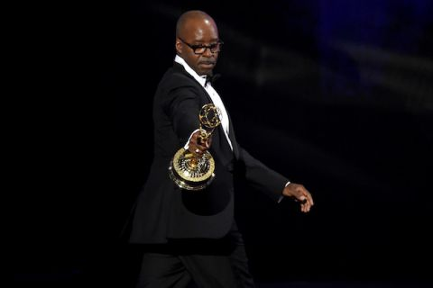 Courtney B. Vance holding golden award statue in black tuxedo with white shirt against black background