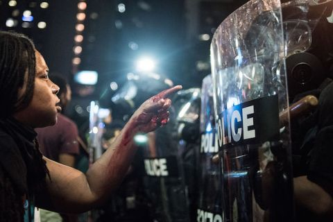Woman with blood on her hand and arm stands in front of police officer in riot gear