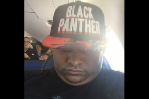 "Woman in black t-shirt and baseball cap with flat red-and-black brim with black top and white lettering reading ""Black Panther"""