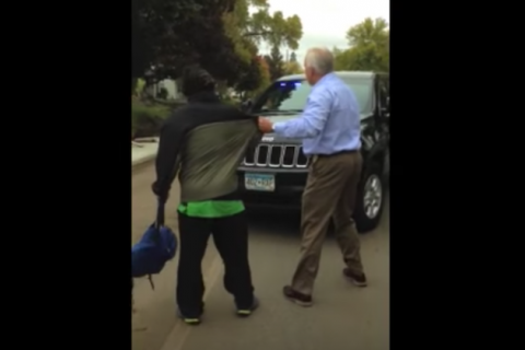 Black man in green jacket near black SUV and White man in light blue shirt and khaki pants