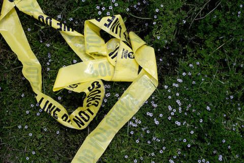 Yellow police tape and broken glass in the grass