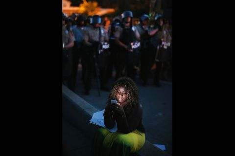 Black woman on phone against dark street and line of police in black riot gear