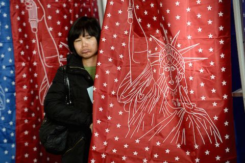 Asian woman peaks out of voting booth curtain.
