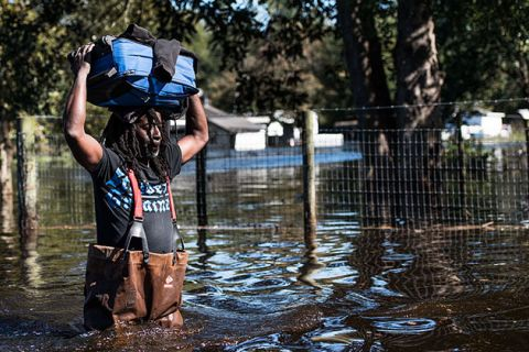 A man carries personal items through a flooded street on October 11, 2016, in Fair Bluff, North Carolina. Thousands of homes have been damaged in North Carolina as a result of Hurricane Matthew, and many are still under threat of flooding.