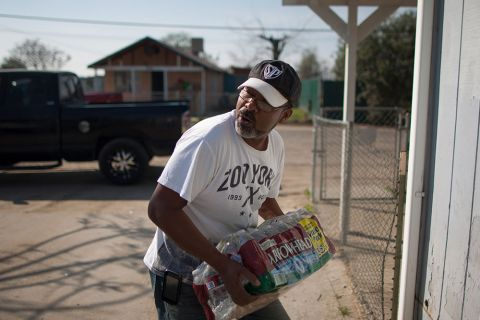 Rafael Surmay receives drinking water on February 11, 2015, from a resident who used to distribute drinking water to neighbors when water wells went dry in East Porterville, California. Now, the state supplies water to the town.