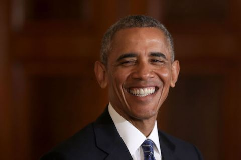 Barack Obama in dark navy suit with white shirt and navy tie with white stripes