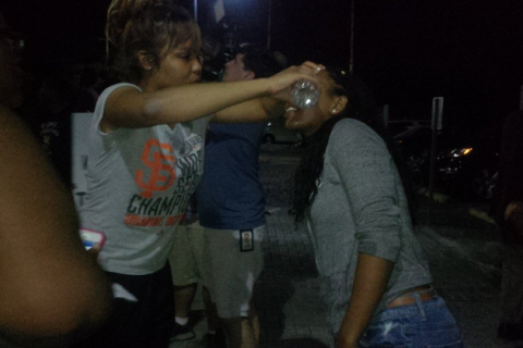 Black woman in grey t-shirt with black and orange lettering pouring water from water bottle into eyes of Black woman in grey hoodie