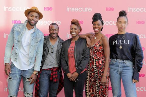 Two Black men in denim and leather jackets stand smiling next to three black women in leather jacket, red dress and black crewneck shirt against pink background