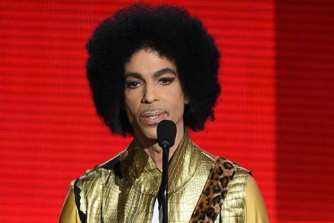 Black man with black afro in gold suit behind black mic against red screen
