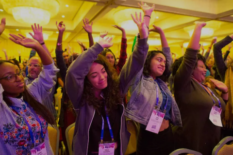 A group of smiling young women raise their arms during a breathing exercise at a session of the Facing Race National Conference