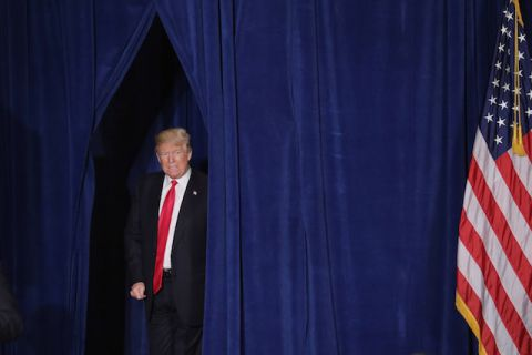 Donald Trump grimaces while emerging from a navy blue curtain.