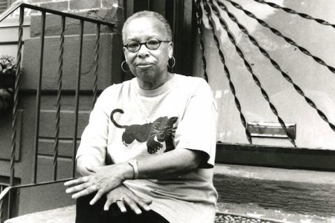 A Black women with short hair wearing a Black Panther Party T-shirt sits on the front steps of a home.