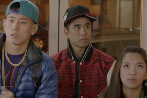 Asian man in light blue baseball cap and blue jacket next to Asian man in black baseball cap and red patterned jacket next to Asian woman in green jacket