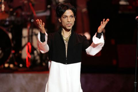Alt-text: Prince in black and white shirt holds up his hands