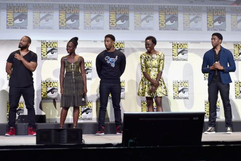 Black in black t-shirt and pants next to Black woman in green dress next to Black man in navy sweatshirt and jeans next to Black woman in black and yellow dress next to Black man in blue blazer with black shirt and slacks, all on grey stage